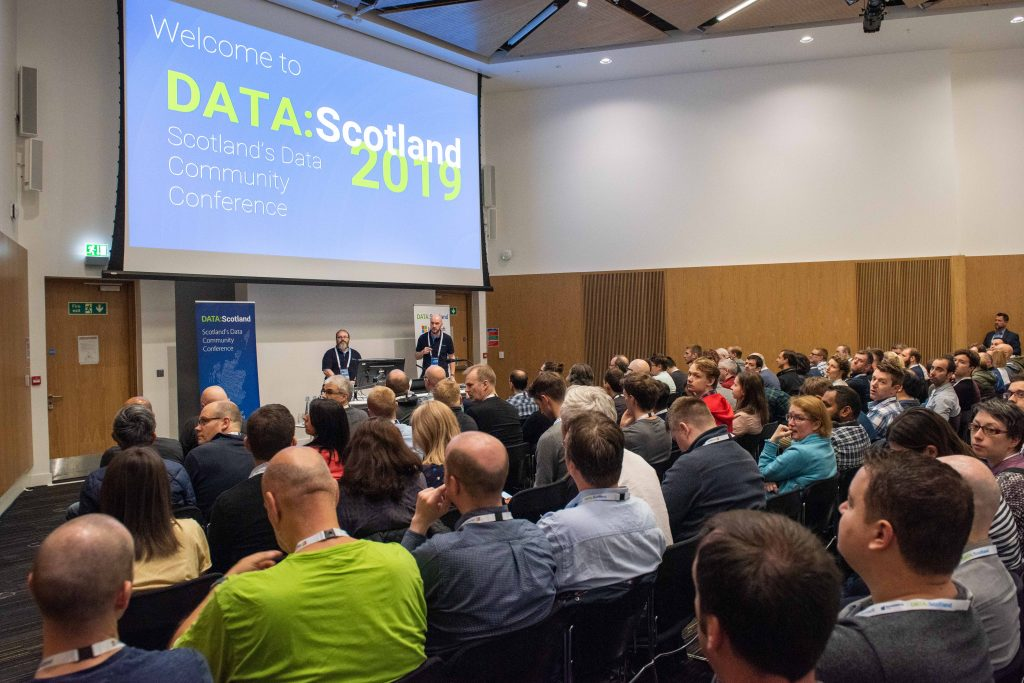 A crowd listen to DATA:Scotland 2019's keynote in a busy theatre